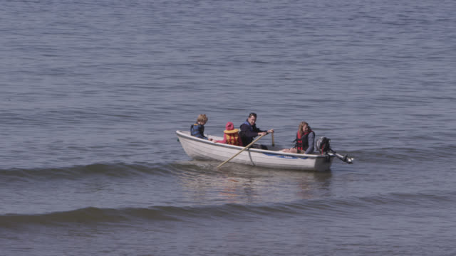Tourists in rowing boat on beach, Devon, England