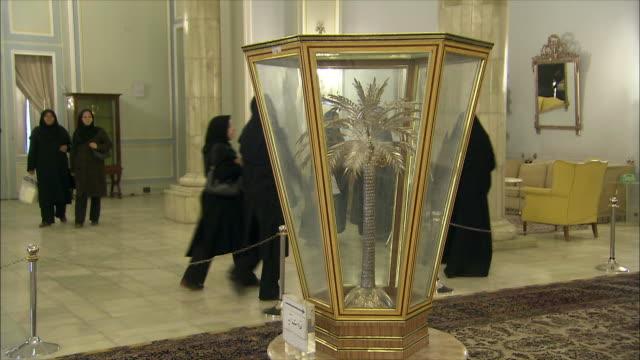 ms tourists in saadabad palace, golden palm tree in glass cabinet in foreground, tehran, iran - skåp med glasdörrar bildbanksvideor och videomaterial från bakom kulisserna
