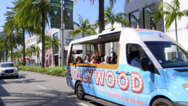 Tourists in sightseeing bus explore Rodeo Drive in Beverly Hills, Los Angeles, California, 4K