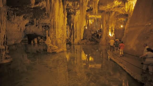 vídeos de stock, filmes e b-roll de ws tourists in stalactite cave neptune's grotto (grotta di nettuno) near alghero / sardinia, italy - grotto cave