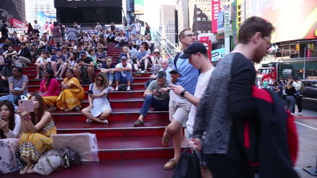 vídeos de stock e filmes b-roll de tourists in times square, new york, u.s. on monday, may 21, 2018. - painel publicitário eletrónico