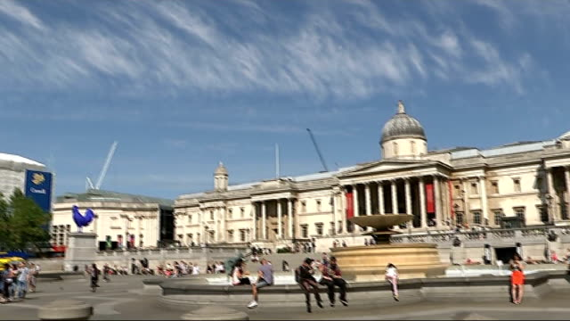 Tourists in Trafalgar Square Golden Tours sightseeing bus along / statue of Admiral Nelson on top of Nelson's Column / tourists on opentop bus /...