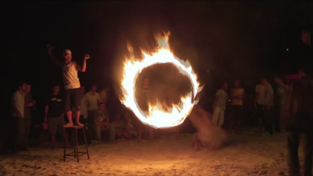 ms zi tourists jumping through ring of fire on beach at night, ko phangan, thailand - ring stock videos and b-roll footage