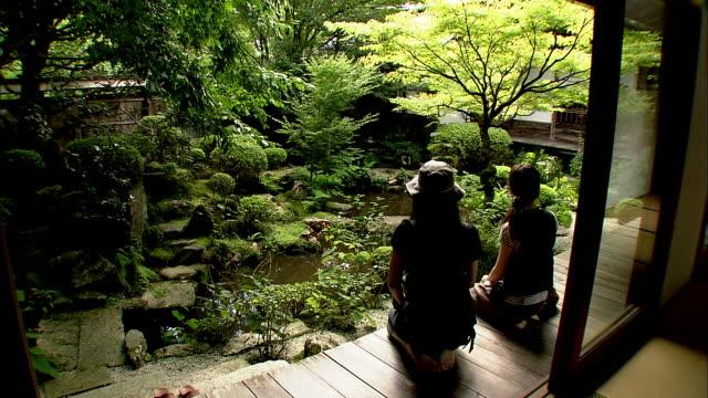 tourists kneel on a deck in the inner garden of hosenin temple. - 整形式庭園点の映像素材/bロール