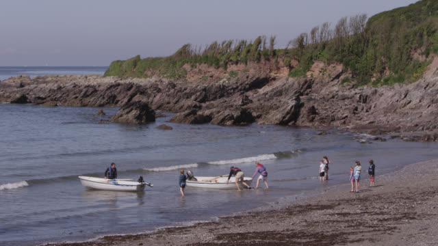 Tourists launch rowing boats on beach, Devon, England