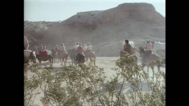 tourists leave dude ranch to go on a trail ride in texas; 1979 - 外乗点の映像素材/bロール
