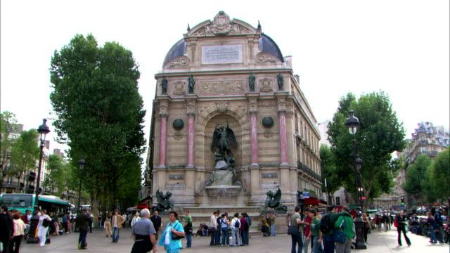 tourists loiter in the place saint michel in paris. - 天使ミカエル点の映像素材/bロール