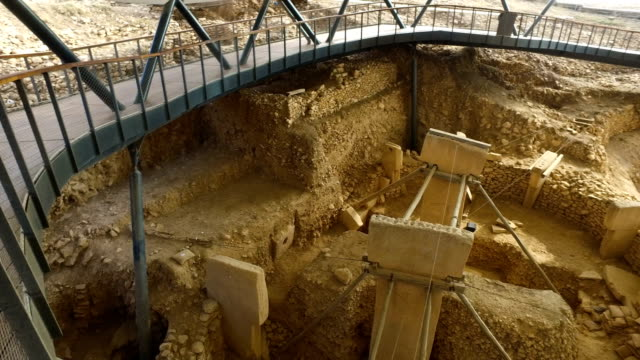 vidéos et rushes de tourists look over t-shaped pillars at the gobekli tepe archaeology site on september 18, 2018 in sanliurfa, turkey. since it's discovery the... - civilisation ancienne