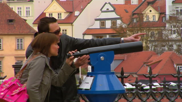 tourists look through a telescope at saint vitus cathedral in prague castle. - cattedrale di san vito video stock e b–roll