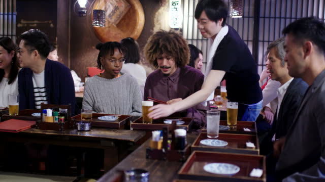 tourists looking at a menu in a japanese izakaya - unhealthy eating stock videos & royalty-free footage