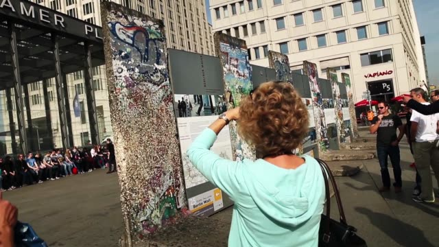 Tourists looking at a section of the Berlin Wall at Potsdamer Platz shot on September 29 2014 in Berlin Germany