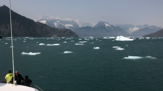 tourists looking at glacier and icebergs from tour boat sailing in alaska - travel stock videos & royalty-free footage