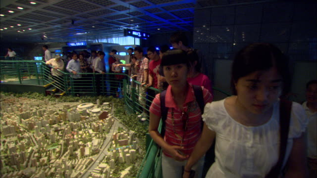 ws pan tourists looking at large scale model of city of shanghai in year 2020 on display at shanghai urban planning museum, shanghai, china - 展覧会点の映像素材/bロール