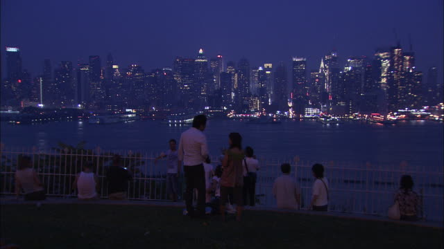 ws, pan, tourists looking at new york city skyline from hamilton park at dusk, weehawken, new jersey, usa - hamilton new york state stock videos & royalty-free footage