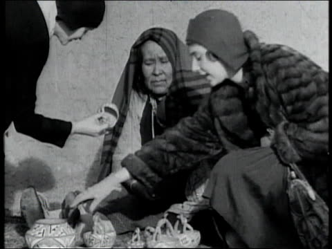 1928 montage tourists looking at souvenirs sold by native americans, then chatting in front of fireplace / united states - 1928 stock-videos und b-roll-filmmaterial