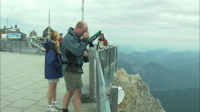 vídeos de stock, filmes e b-roll de ws pan ha tourists looking at view from zugspitze mountain peak, bavaria, germany - montanhas wetterstein