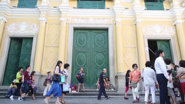 tourists mingling outside st dominics church, a tour guide leads korean tourists outside st dominics church in macau, a clothes vendor arranges... - leal senado square stock videos & royalty-free footage