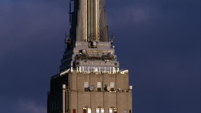 Tourists move about on top of the Empire State Building set against a dark, moody sky.
