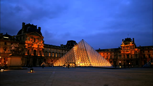 tourists move around the plaza in front of the louvre in paris. - louvre stock videos and b-roll footage
