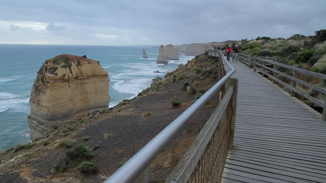 ms tourists moving at great ocean road in front of twelve apostles at dusk / port campbell, victoria, australia - port campbell national park stock videos & royalty-free footage