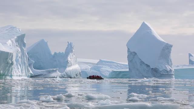 Tourists moving through Icebergs in small zodiac boat, Antarctica