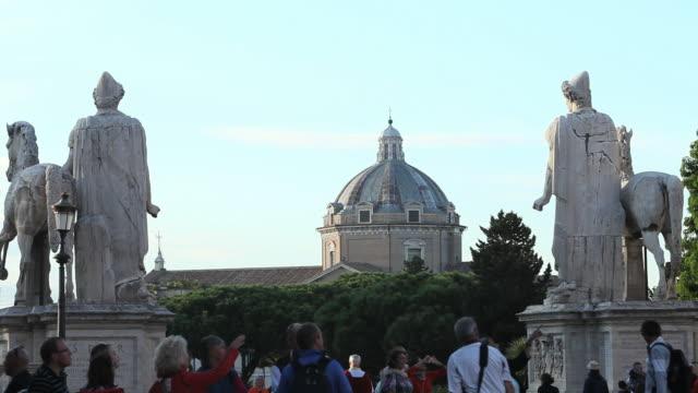 ms tourists near castor and pollux statues with church of gesu dome in background / rome, italy - rappresentazione di animale video stock e b–roll