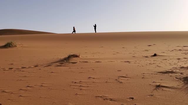 vídeos de stock, filmes e b-roll de tourists on a sand dune in the distance - local de filmagem não americano