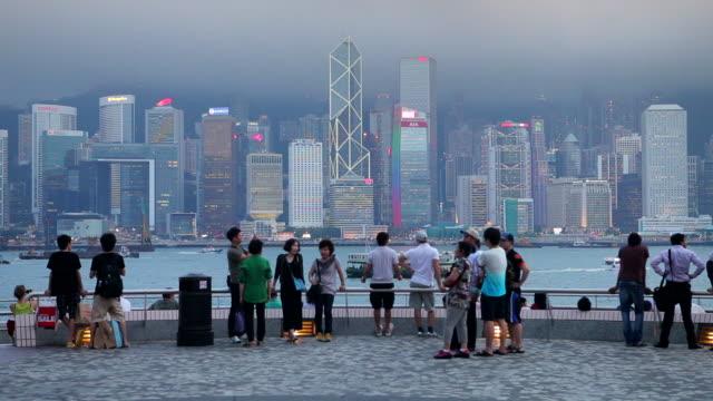 tourists on a waterfront view the hong kong skyline. - ビクトリアピーク点の映像素材/bロール