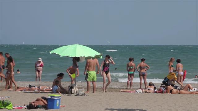 stockvideo's en b-roll-footage met tourists on adriatic beach - zonnescherm gefabriceerd object