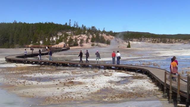 vídeos de stock e filmes b-roll de tourists on boardwalk at norris geyser basin, autumn in yellowstone national park - piscina térmica
