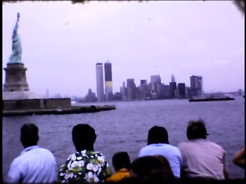 / tourists on boat in harbor statue of liberty and world trade center building under construction on january 01 1970 in new york new york - statue of liberty new york city stock-videos und b-roll-filmmaterial