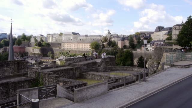 tourists on bock cliff in luxembourg with skyline in background - spoonfilm stock-videos und b-roll-filmmaterial