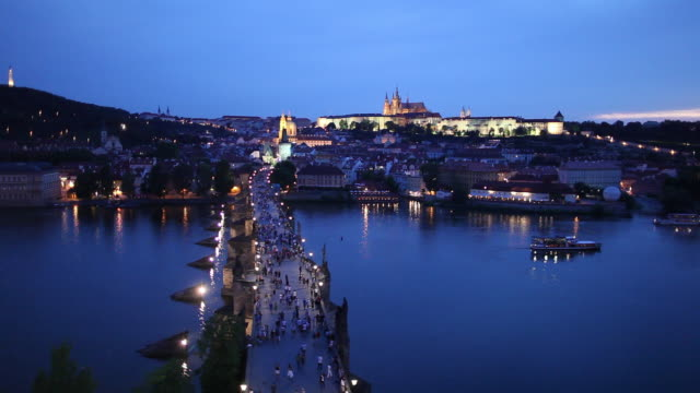 ws ha tourists on charles bridge at dusk, hradcany castle in distance / prague, czech republic - hradcany castle stock videos and b-roll footage