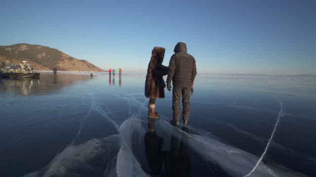 tourists on frozen lake baikal against clear blue sky during sunset - tourism点の映像素材/bロール