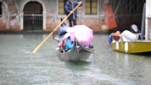 Tourists on gondola under heavy rain. Venice, Italy.