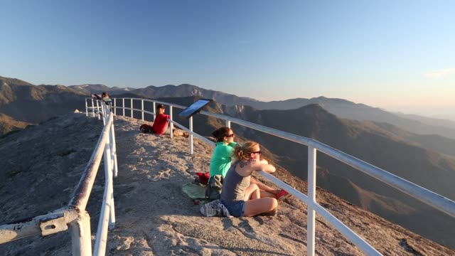 tourists on moro rock, a granite peak outlook in sequoia national park, california, usa, at sunset. - young women stock videos & royalty-free footage
