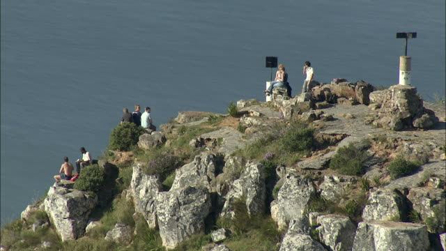 aerial tourists on peak of lion's head, cityscape in background, cape town, western cape, south africa - ライオンズヘッド点の映像素材/bロール