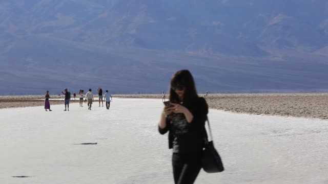 tourists on salt pans badwater in death valley which is the lowest hottest driest place in the usa with an average annual rainfall of around 2 inches... - death valley nationalpark stock-videos und b-roll-filmmaterial