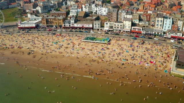 tourists on south bay beach, scarborough, north yorkshire, england - 英国スカーブラ点の映像素材/bロール