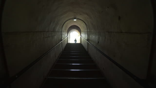 tourists on staircase exiting tunnel at historic minglou tower - beijing, china - tunnel video stock e b–roll
