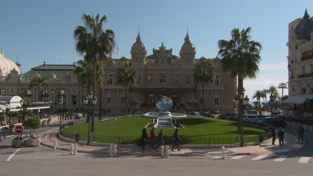 tourists on street near casino monte-carlo in city against blue sky during sunny day - monte carlo, monaco - natural parkland stock videos & royalty-free footage