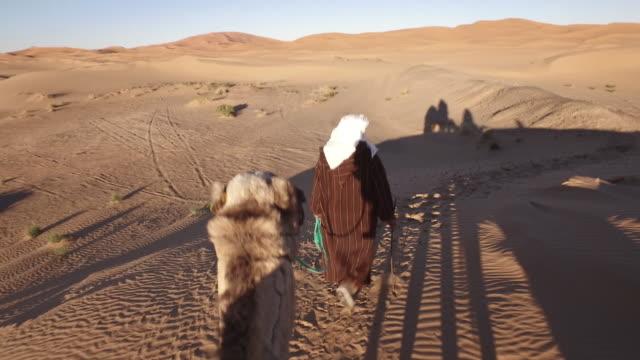 vídeos y material grabado en eventos de stock de turistas en tren de camellos en el sahara dirigido por guía - duna de arena
