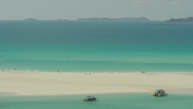 Tourists on Whitehaven Beach with pan.