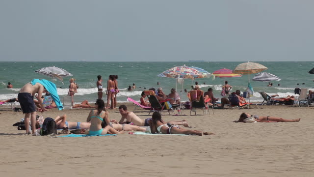 stockvideo's en b-roll-footage met tourists & parasols on beach - zonnescherm gefabriceerd object