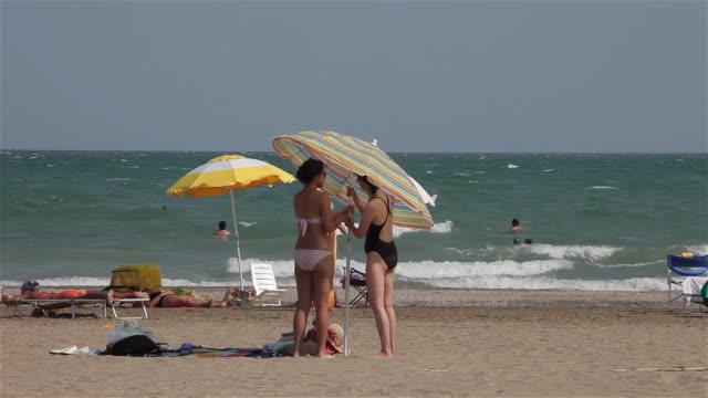 stockvideo's en b-roll-footage met tourists & parasols on beach - zonwering