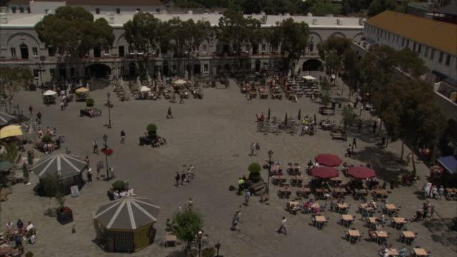 tourists pass a sidewalk cafe in a plaza in gibraltar. available in hd - gibraltar bildbanksvideor och videomaterial från bakom kulisserna