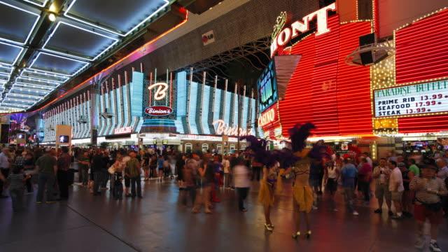vidéos et rushes de tourists pass by showgirls making an appearance at the fremont street experience. - las vegas
