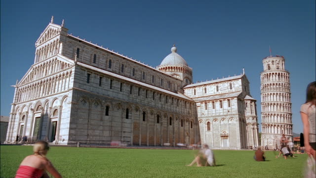 tourists photograph the cathedral of pisa and the leaning tower of pisa from the piazza dei miracoli in italy. - pisa cathedral stock videos & royalty-free footage