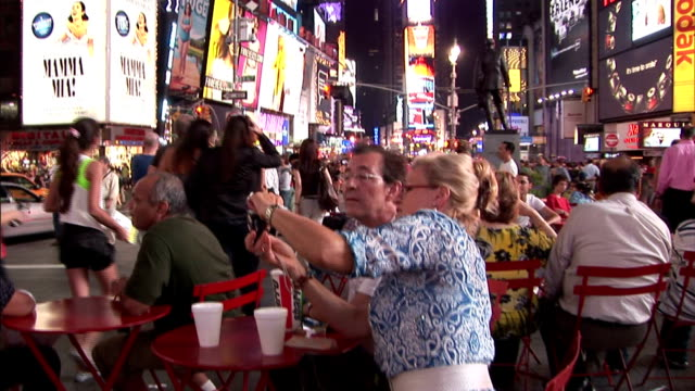 Tourists photograph the lights of Times Square near George M. Cohan's Give My Regards to Broadway statue in New York City at night.