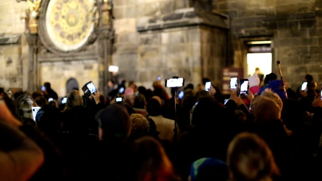 Tourists photographing astronomical clock in Prague